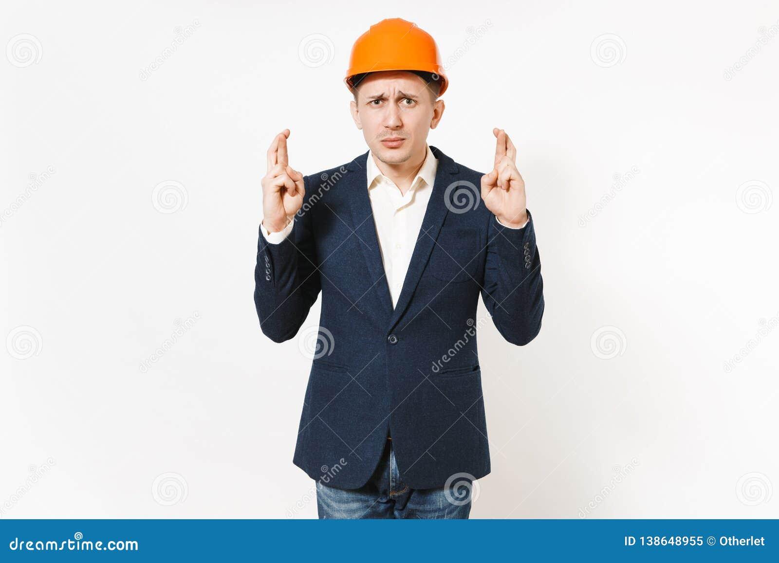 Uomo d affari responsabile in vestito scuro, nel casco protettivo della costruzione tenenti le dita speciale attraversato ed aspe