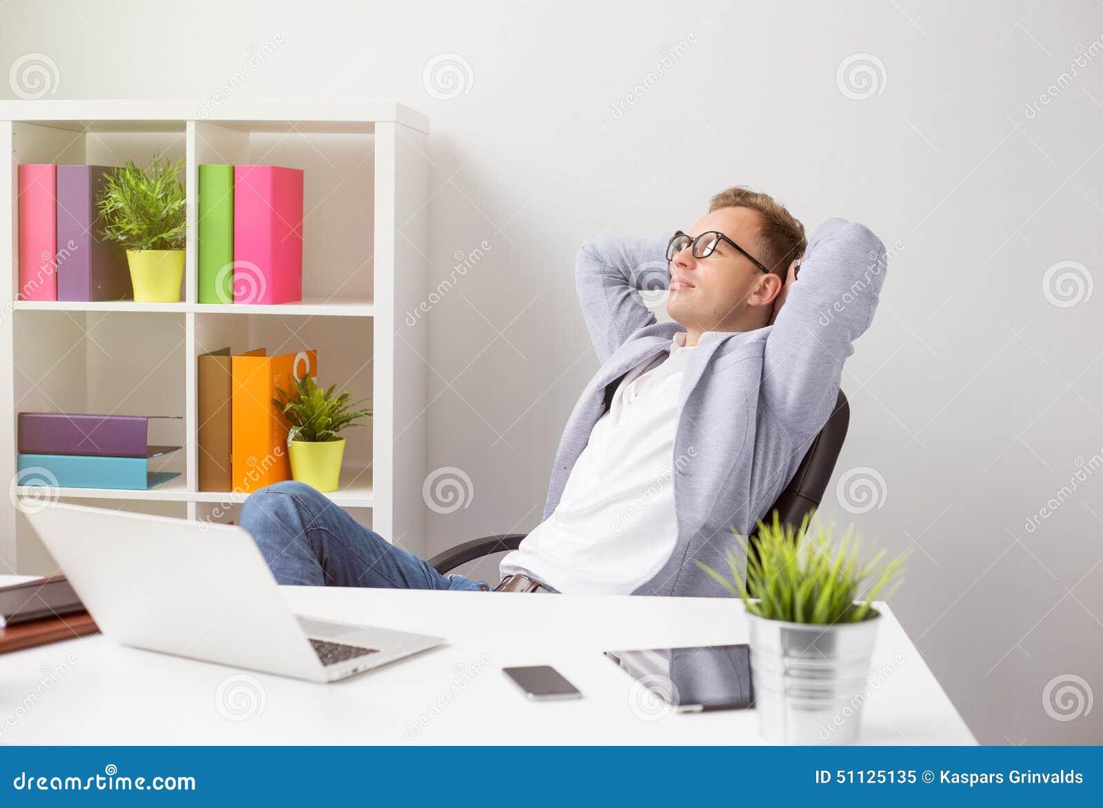 Uomo d affari rilassato che si siede nella sedia con le mani dietro la testa