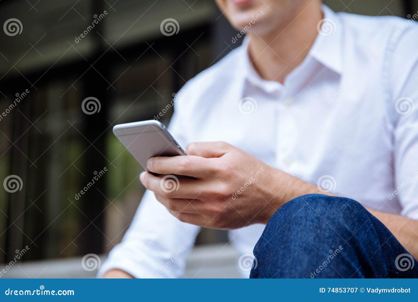 Uomo d affari in seduta della camicia ed usando telefono cellulare bianchi all aperto