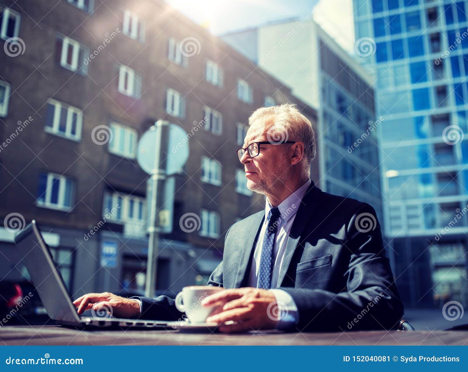 Uomo d affari senior con il caff? bevente del computer portatile