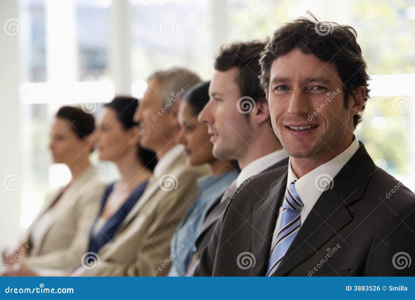 Uomo d affari sicuro con la squadra che cammina oltre lui