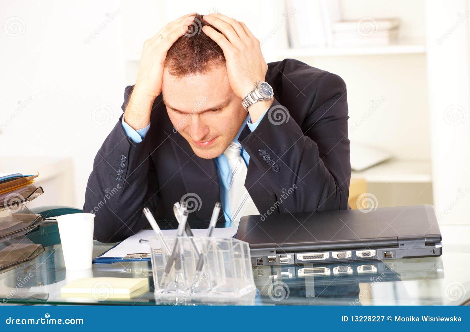 Uomo d affari sollecitato che si siede allo scrittorio