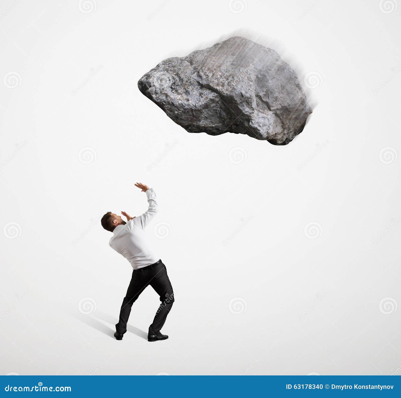 Uomo d affari spaventato sotto la grande pietra di volo