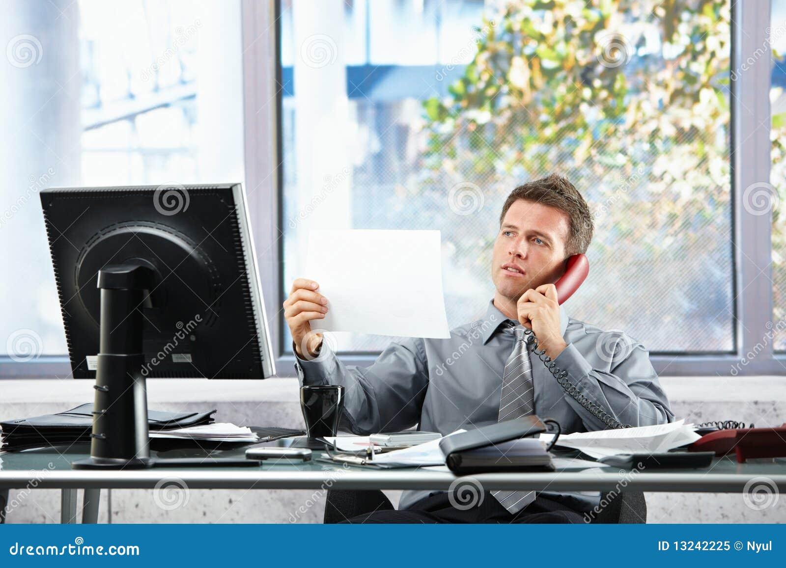 Uomo d affari sulla chiamata che esamina documento