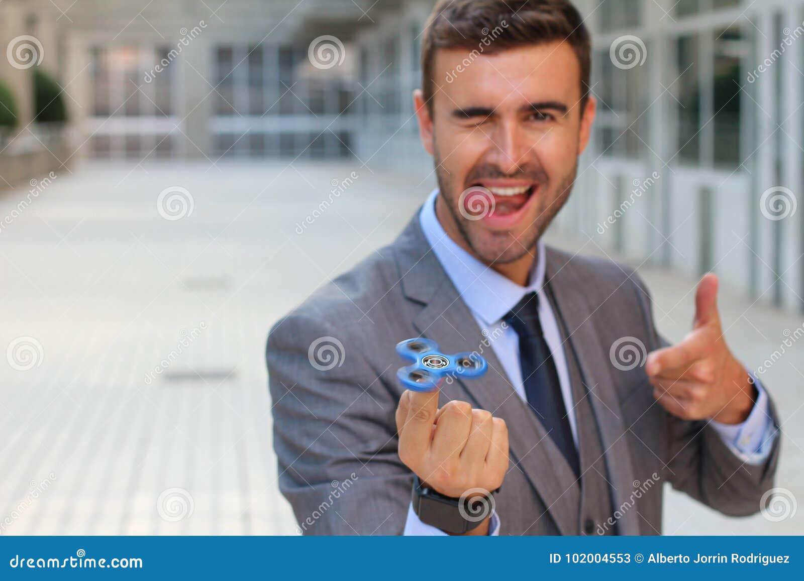 Uomo d affari sveglio che gioca con un filatore della mano