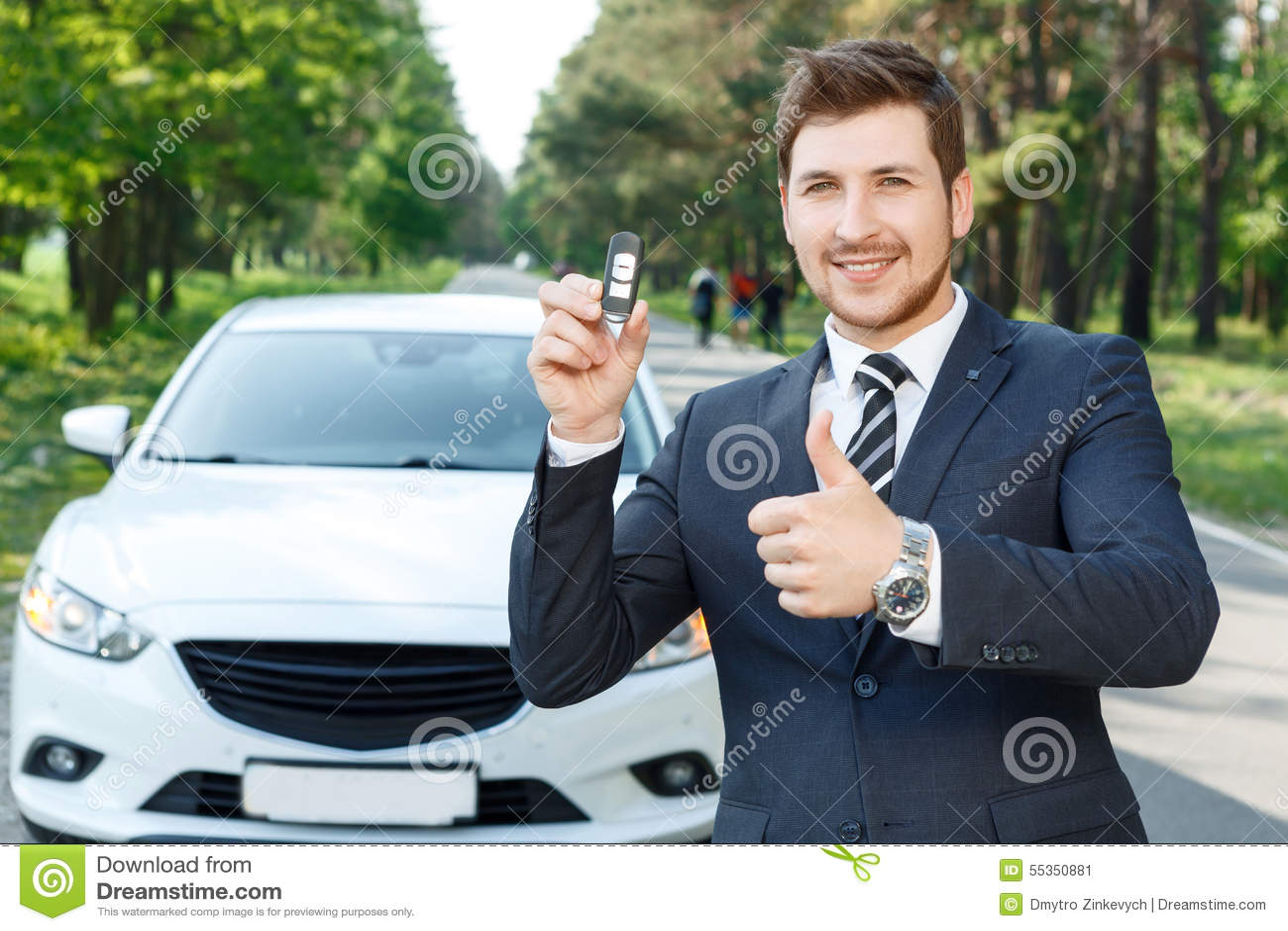 Uomo d affari vicino all automobile che sfoglia su con le chiavi