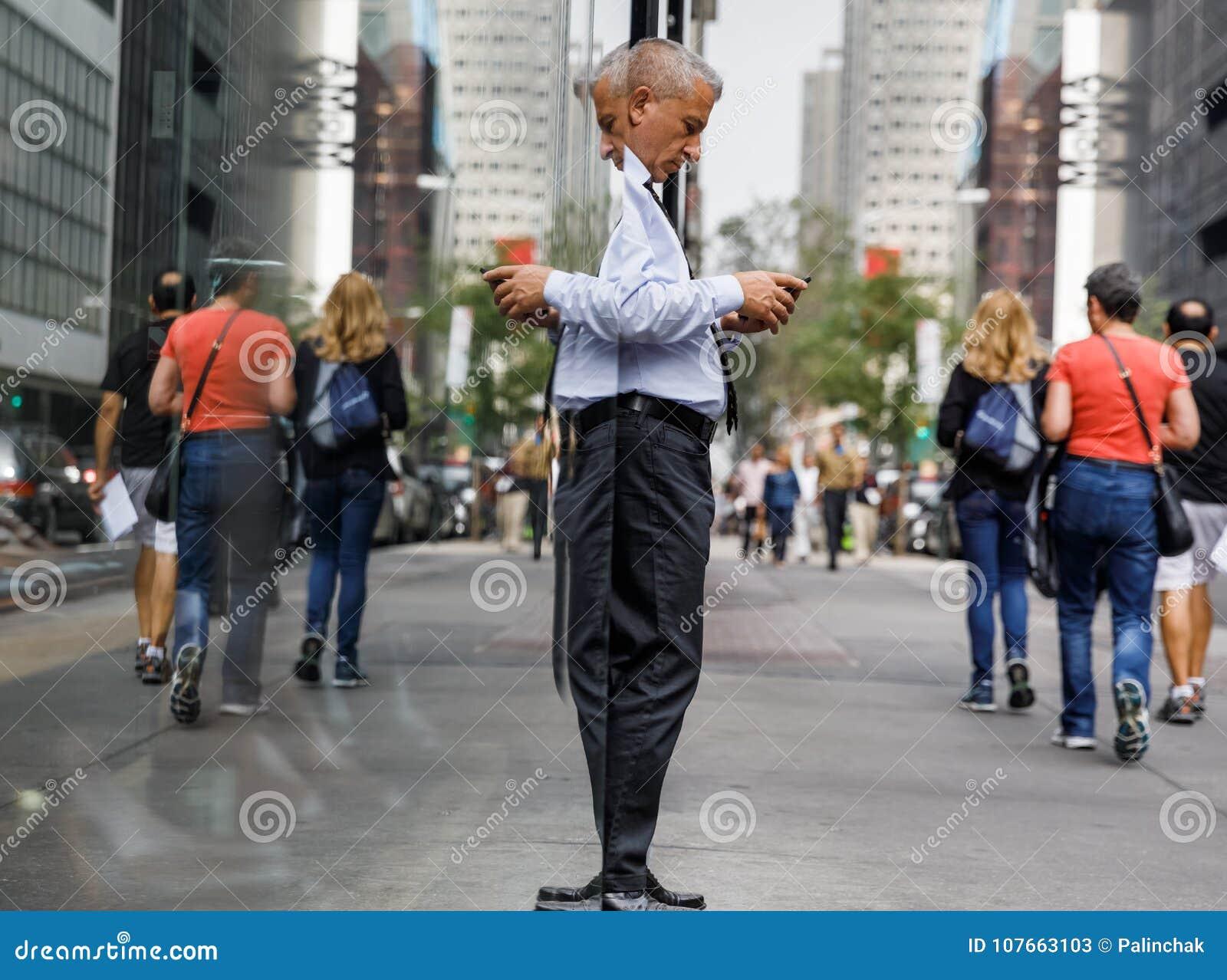 Uomo dai capelli grigi anziano con un telefono cellulare in NYC