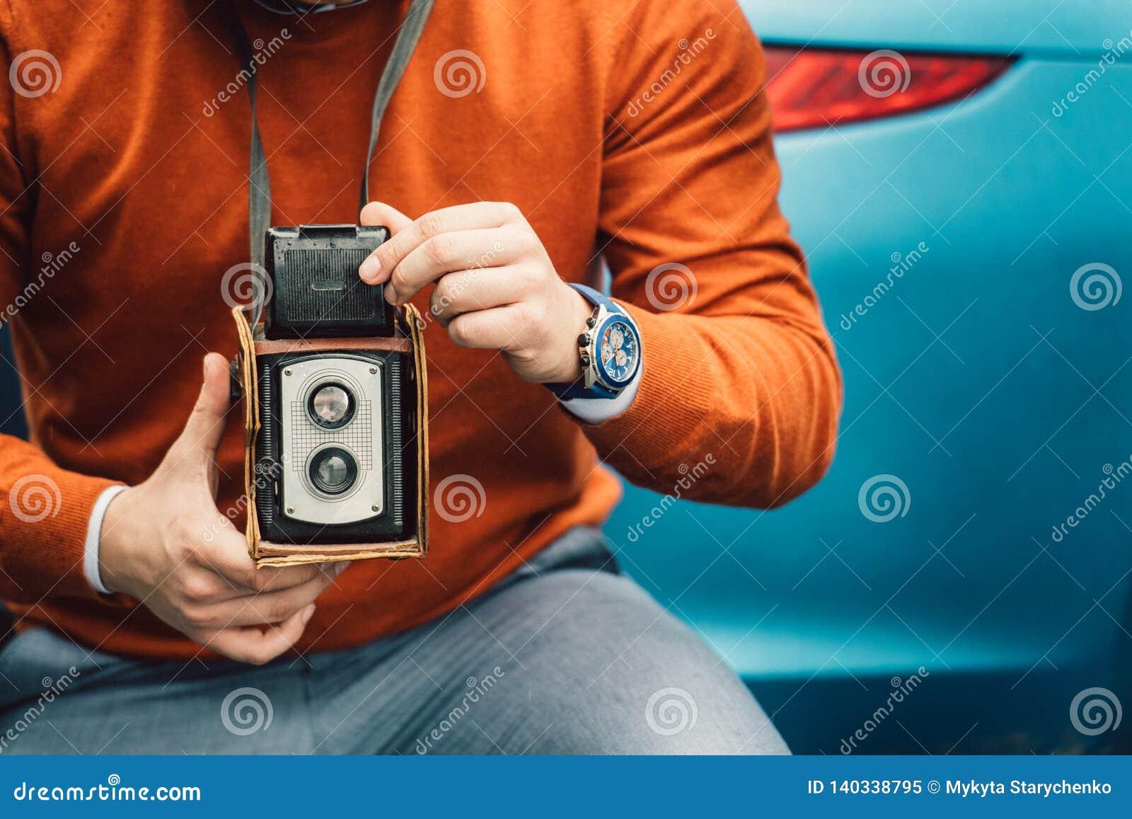 Uomo del fotografo che prende foto con la vecchia macchina fotografica d annata