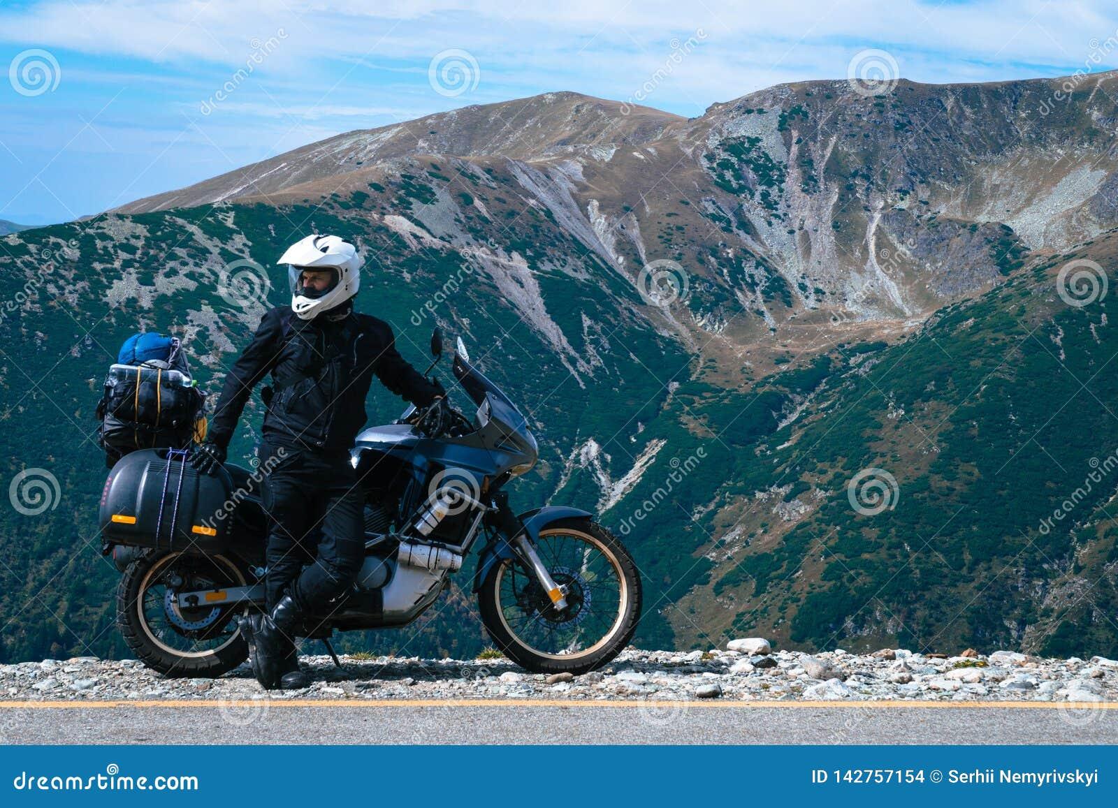Uomo del motociclista e motocicletta di avventura sulla cima della montagna Viaggio del motociclo Mondo che viaggia, vacanze di v