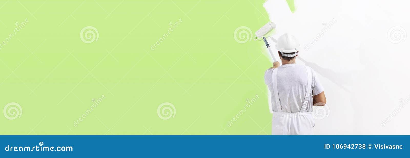 Uomo del pittore sul lavoro con un rullo di pittura, parete che dipinge passo verde