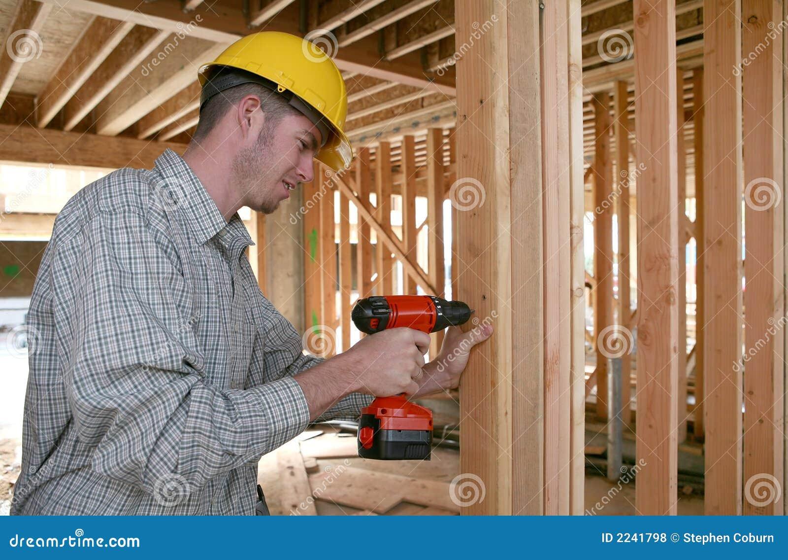 Uomo della costruzione che per mezzo del trivello