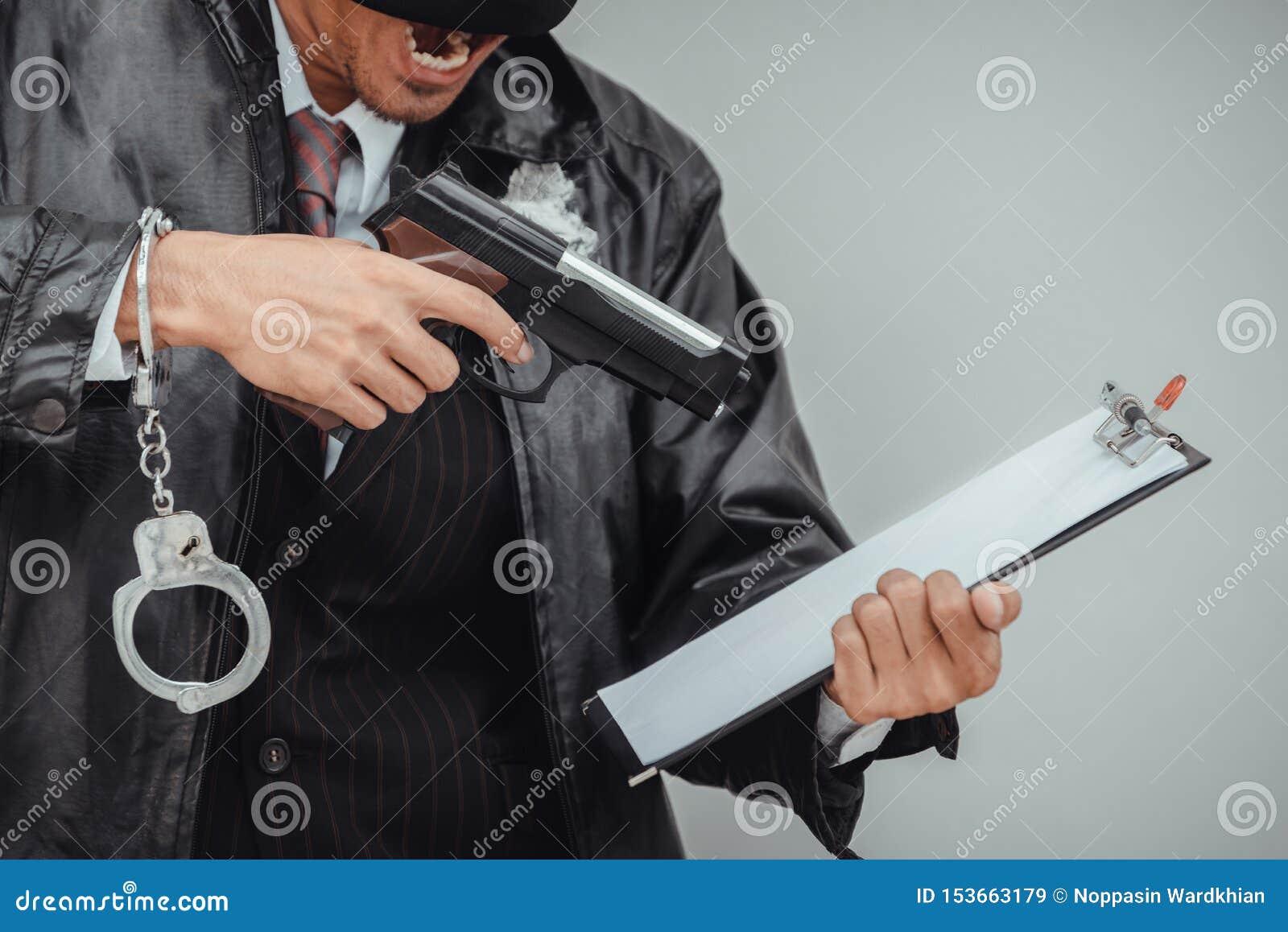 Uomo della mafia in vestito che conta pistola su fondo bianco L uomo d affari arrabbiato ha distrutto gli effetti personali