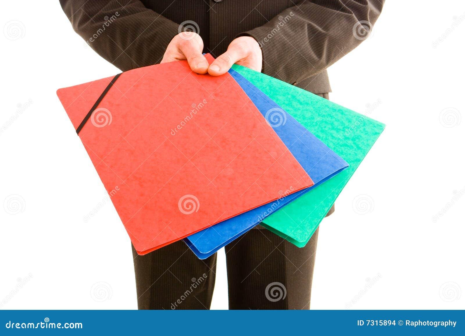 Uomo di affari che tiene tre dispositivi di piegatura colourful