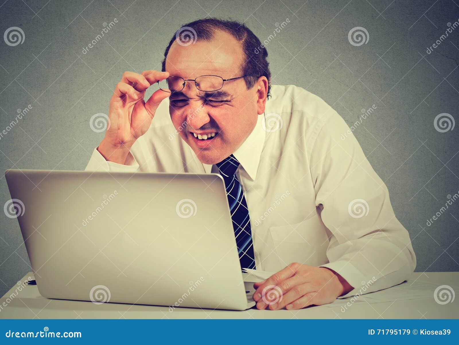 Uomo di affari con i vetri che hanno problemi di vista sconcertanti con il software del computer portatile