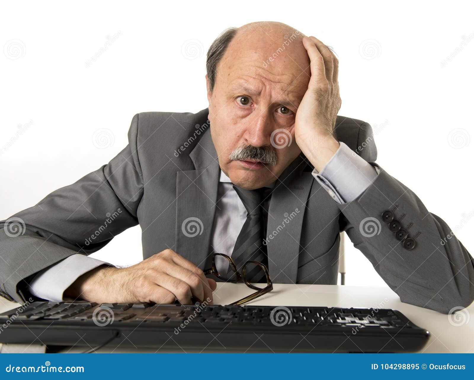 Uomo di affari con la testa calva sul suo funzionamento 60s sollecitato e frustrato allo scrittorio del computer portatile del co