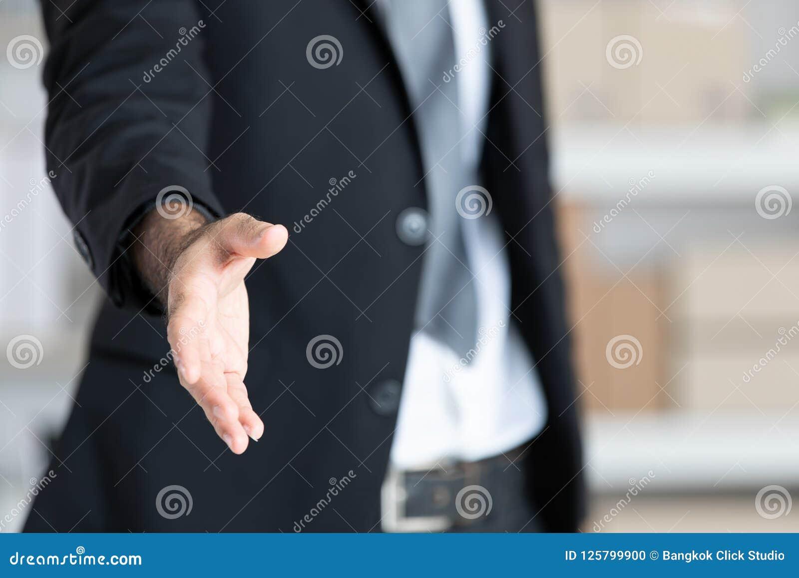 Uomo di affari in mano aperta del vestito nero pronta a stringere le mani, parità