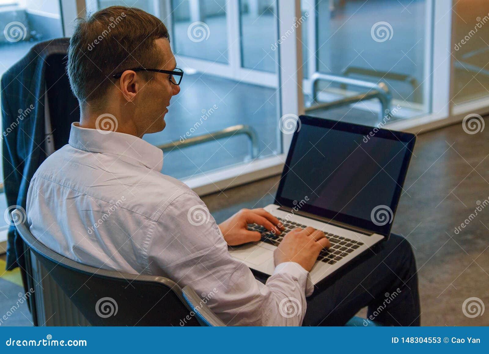 Uomo di affari nel funzionamento bianco su un computer portatile facendo uso di Internet di Wi-Fi in aeroporto