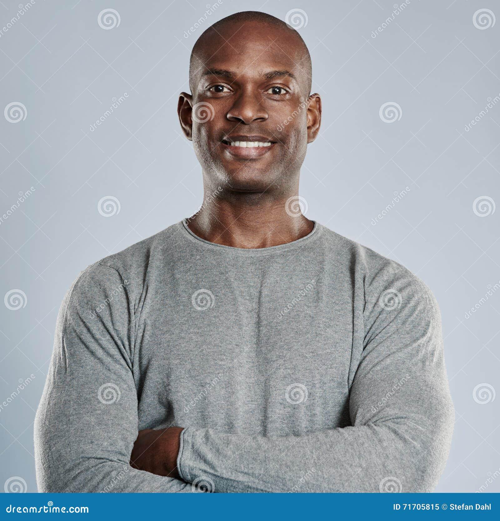 Uomo di colore sicuro con il sorriso piacevole nel gray