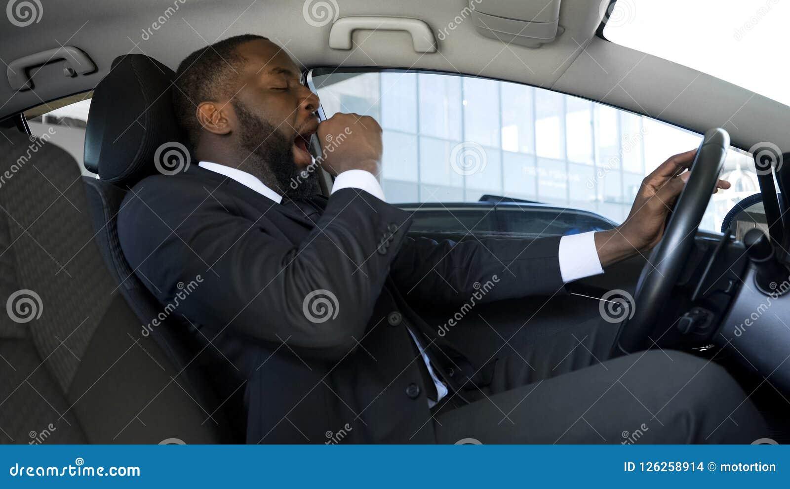 Uomo di colore stanco che sbadiglia in automobile, uomo d affari sovraccarico che conduce automobile, il pericolo