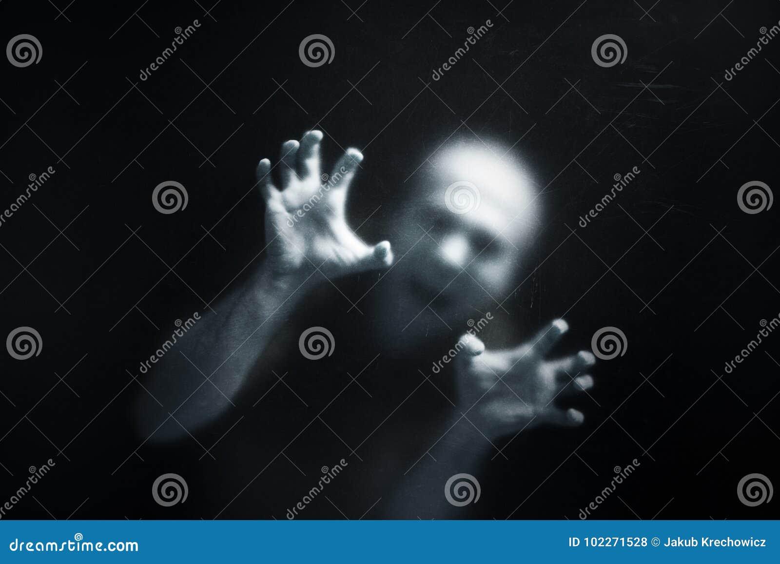 Uomo di grido dietro un vetro