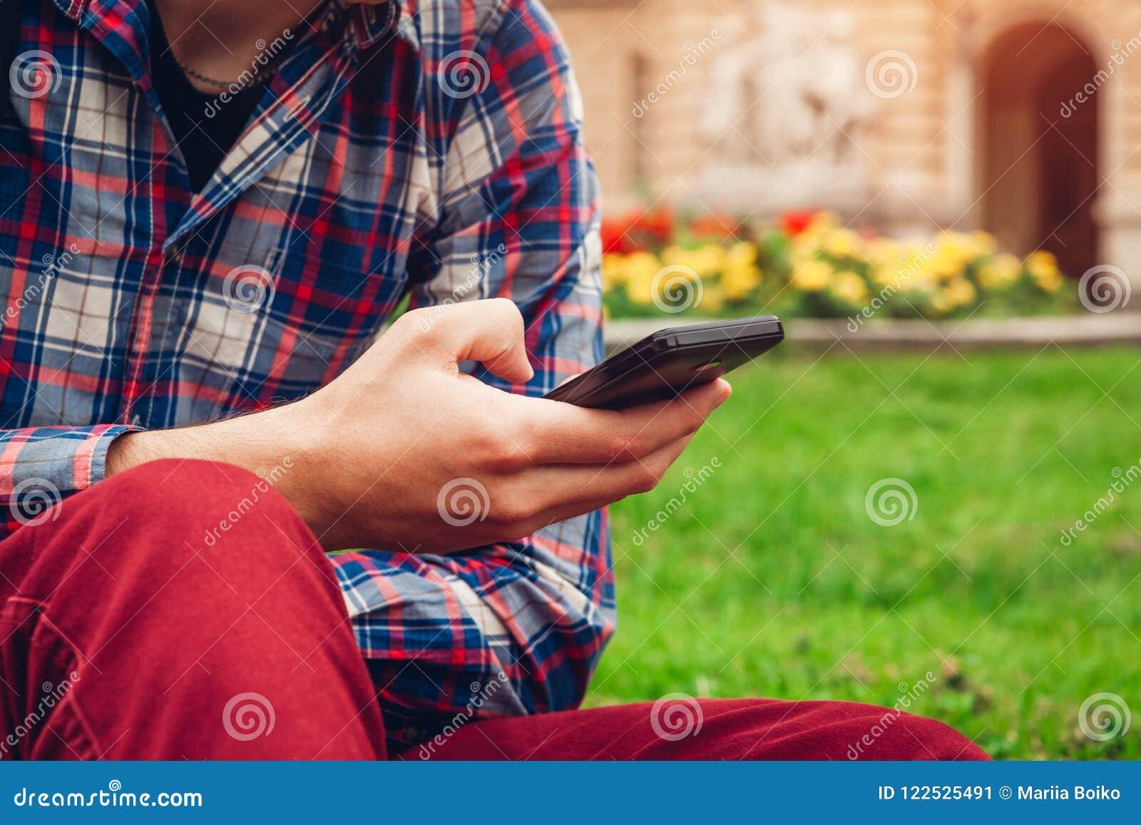 Uomo di istituto universitario bello che raffredda nel parco della città universitaria di primavera Studente felice del tipo che