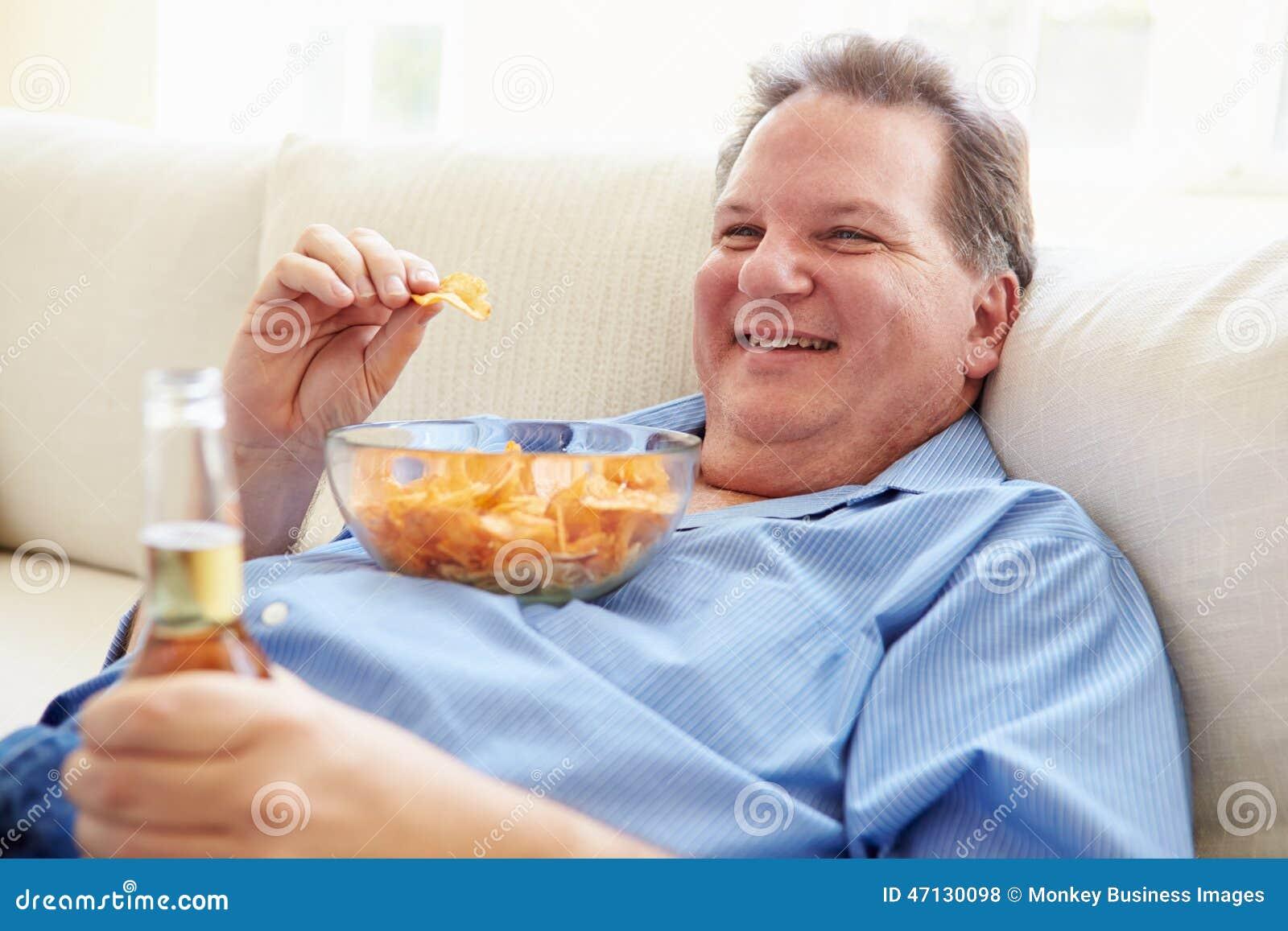 Uomo di peso eccessivo a casa che mangia Chips And Drinking Beer