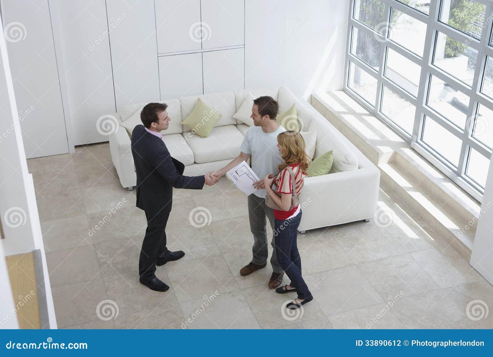 Uomo di Shaking Hands With dell agente immobiliare dalla donna nella nuova casa