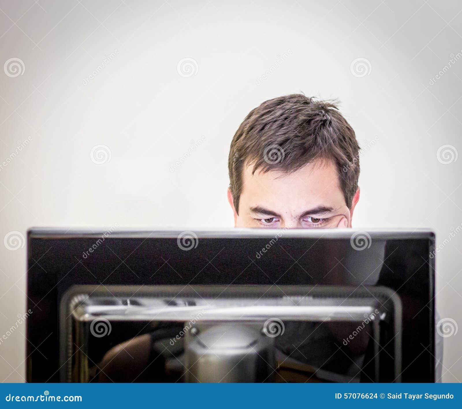 Uomo dietro il monitor di un computer dello scrittorio