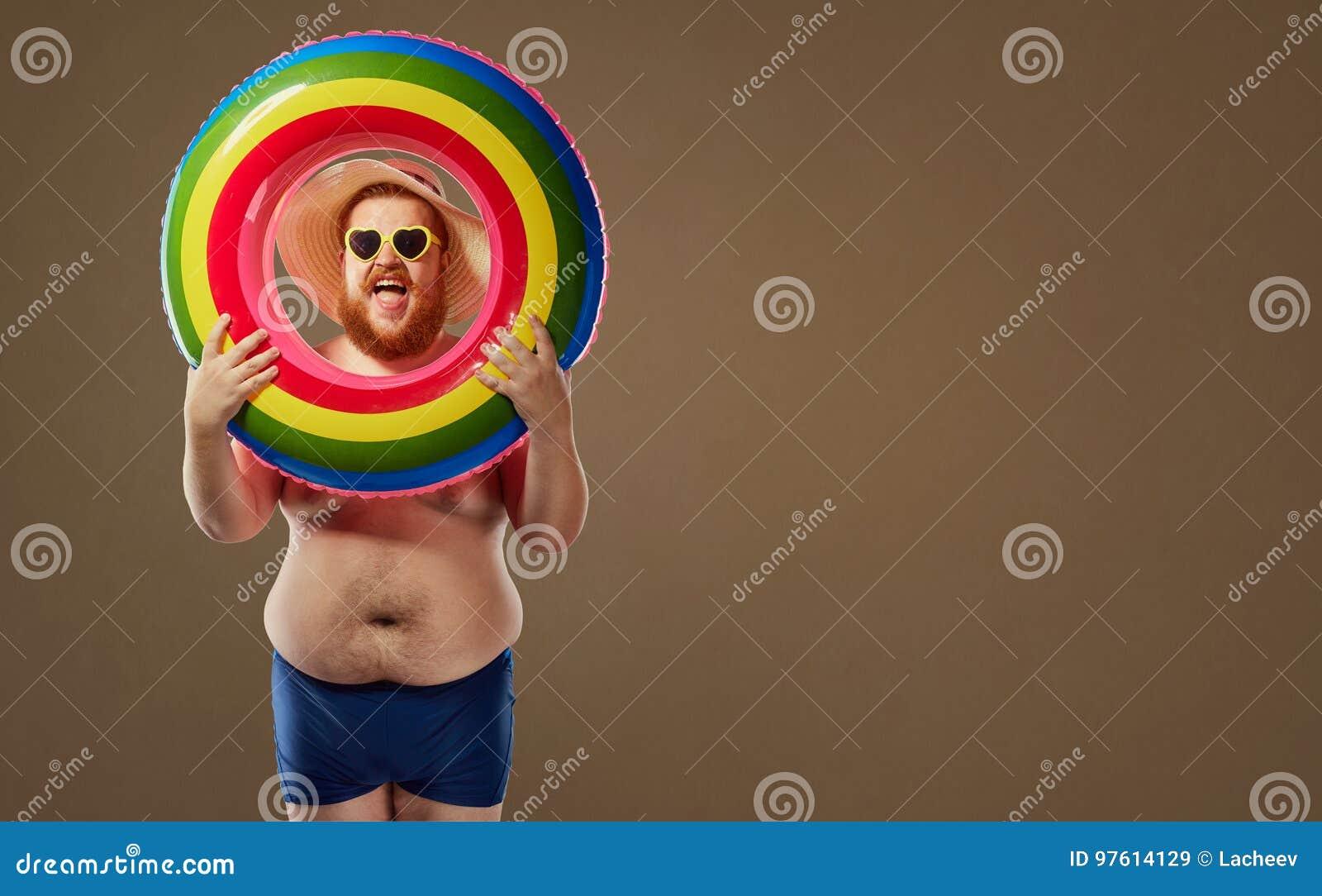 Uomo divertente spesso che sorride in un costume da bagno con un cerchio gonfiabile
