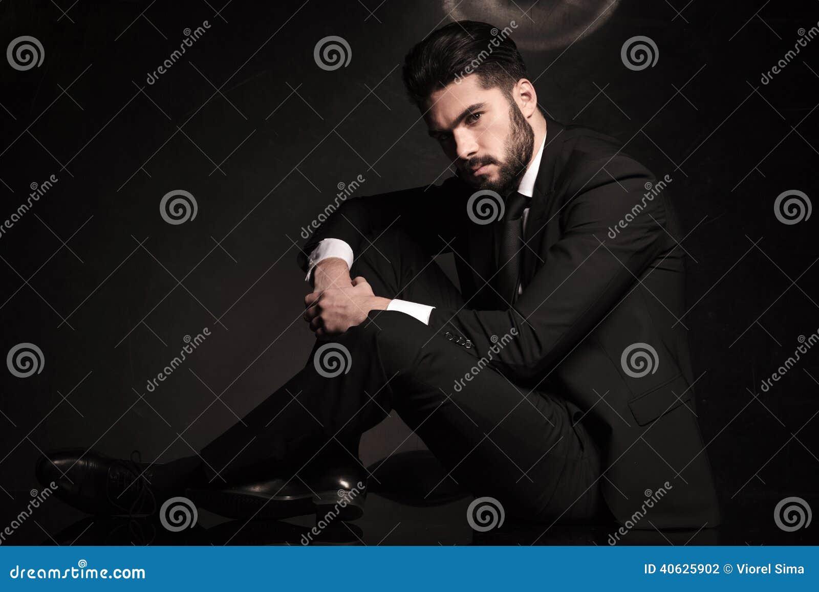 Uomo drammatico di affari che si siede sul pavimento