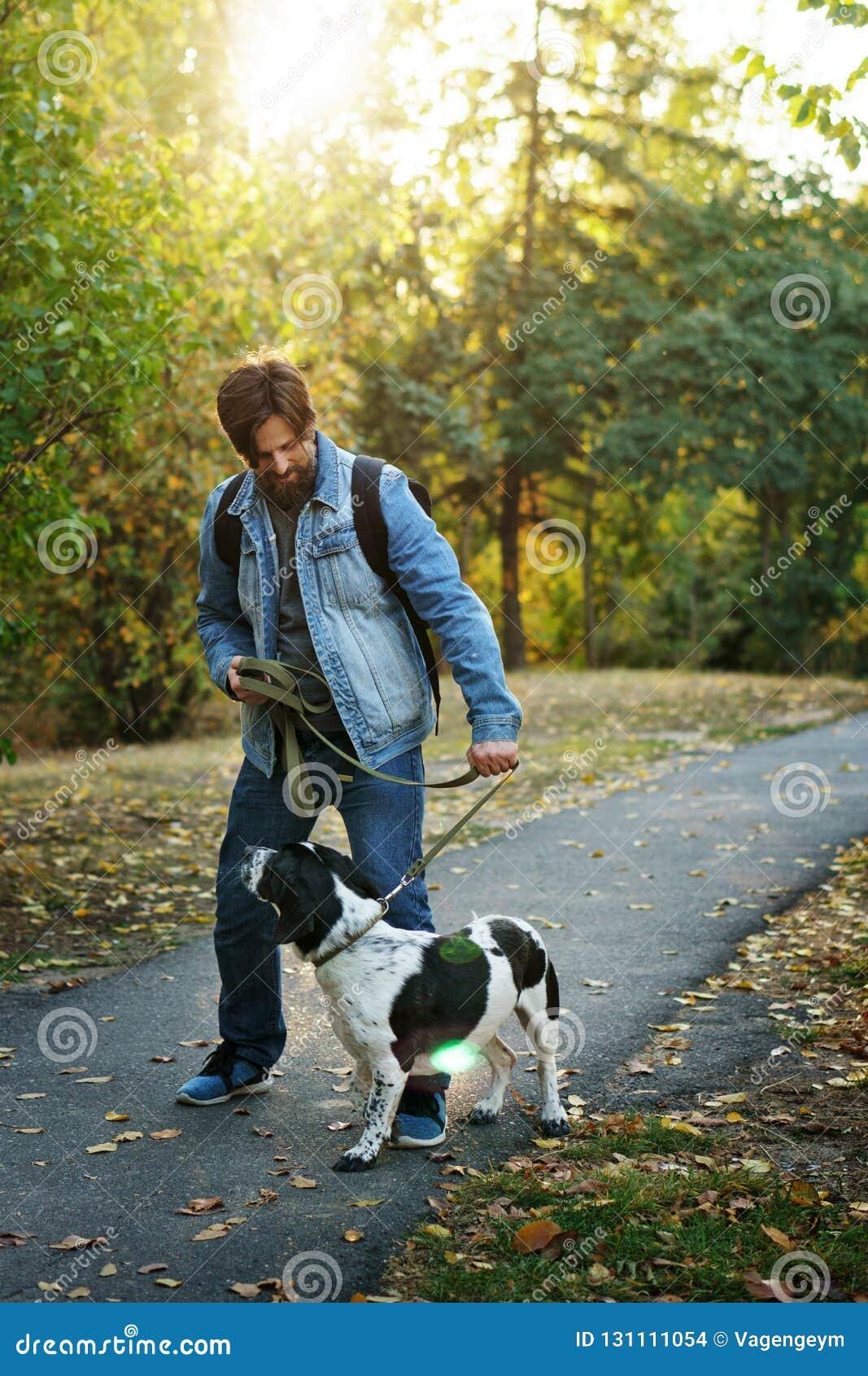 Uomo e cane nel parco di autunno