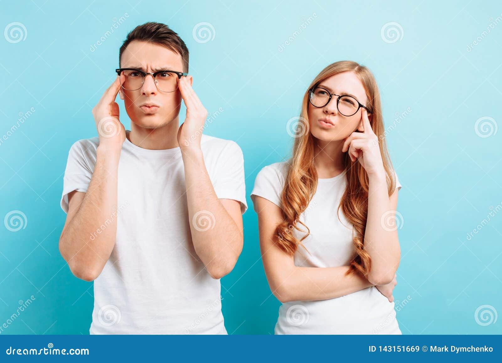 Uomo e donna con i vetri, messi a fuoco e pensierosi, su un fondo blu-chiaro