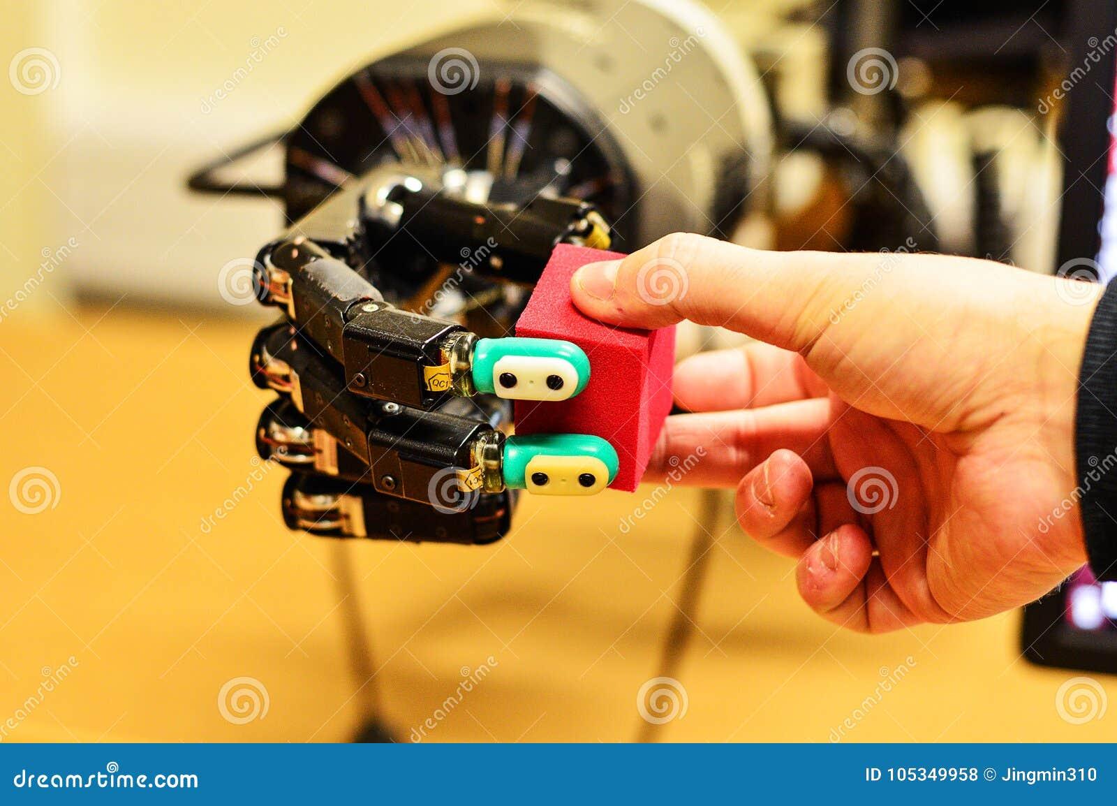 Uomo e mano meccanica che tengono un cubo rosso nel laboratorio di ricerca