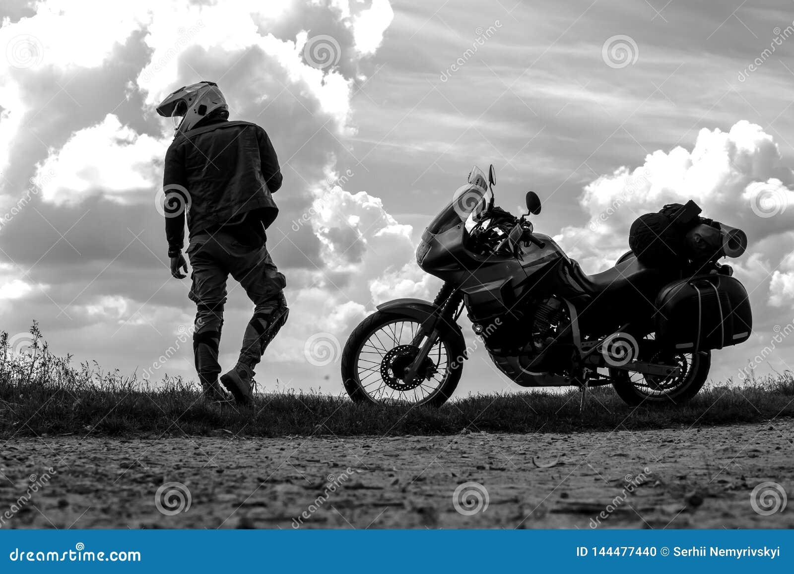Uomo e turista del motociclista fuori dal motociclo della strada con il cavaliere del giovane delle borse laterali da riposare du