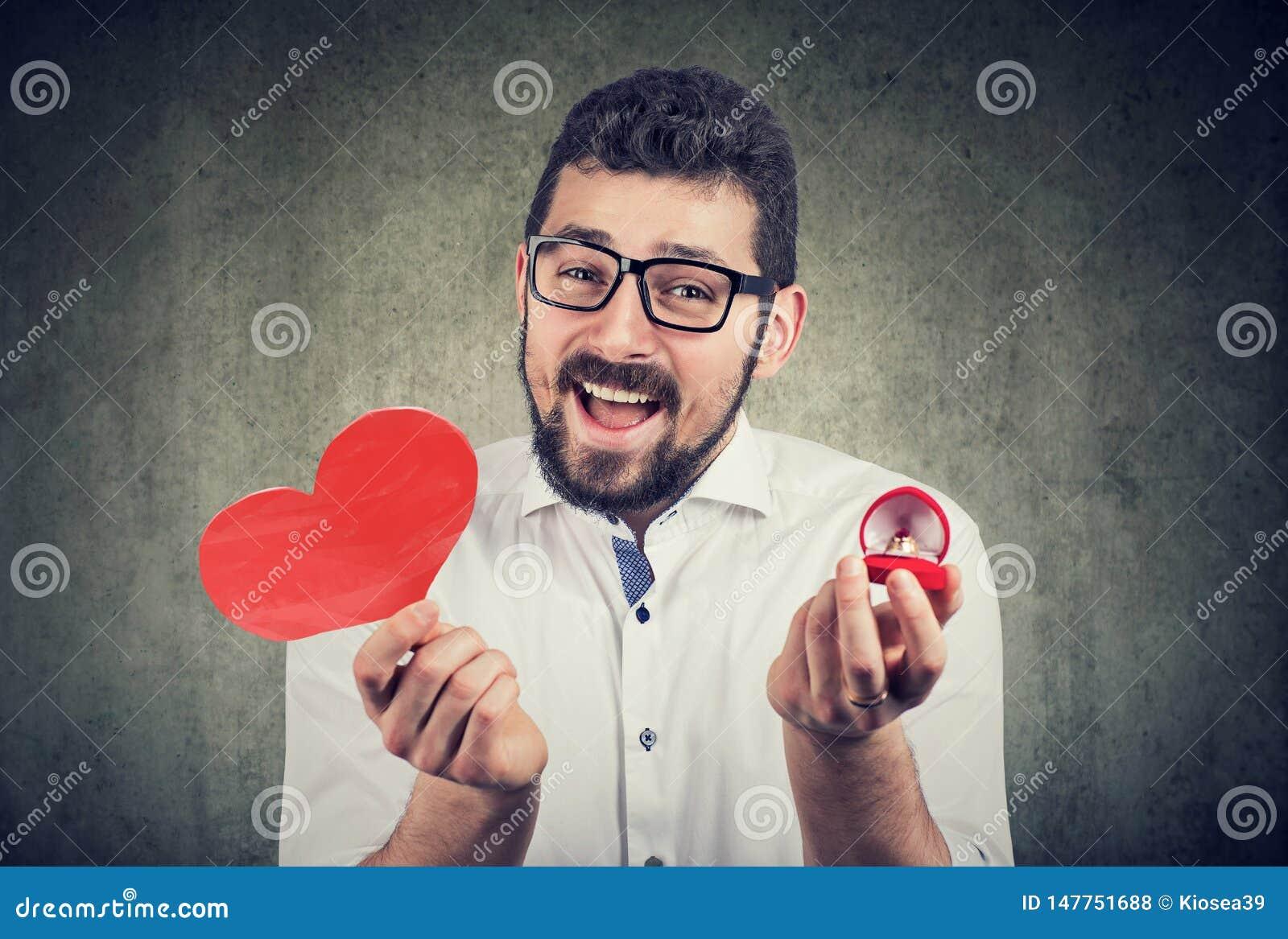 Uomo emozionante eccellente con il contenitore rosso di fede nuziale di forma del cuore