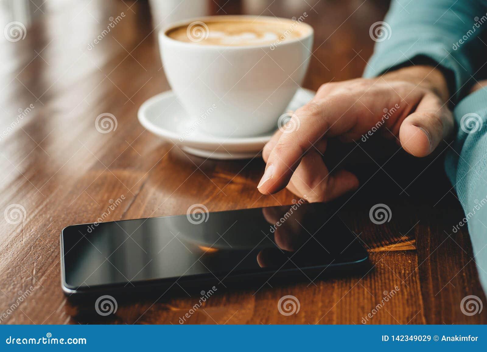 Uomo facendo uso di uno smartphone e bere il fondo del caffè