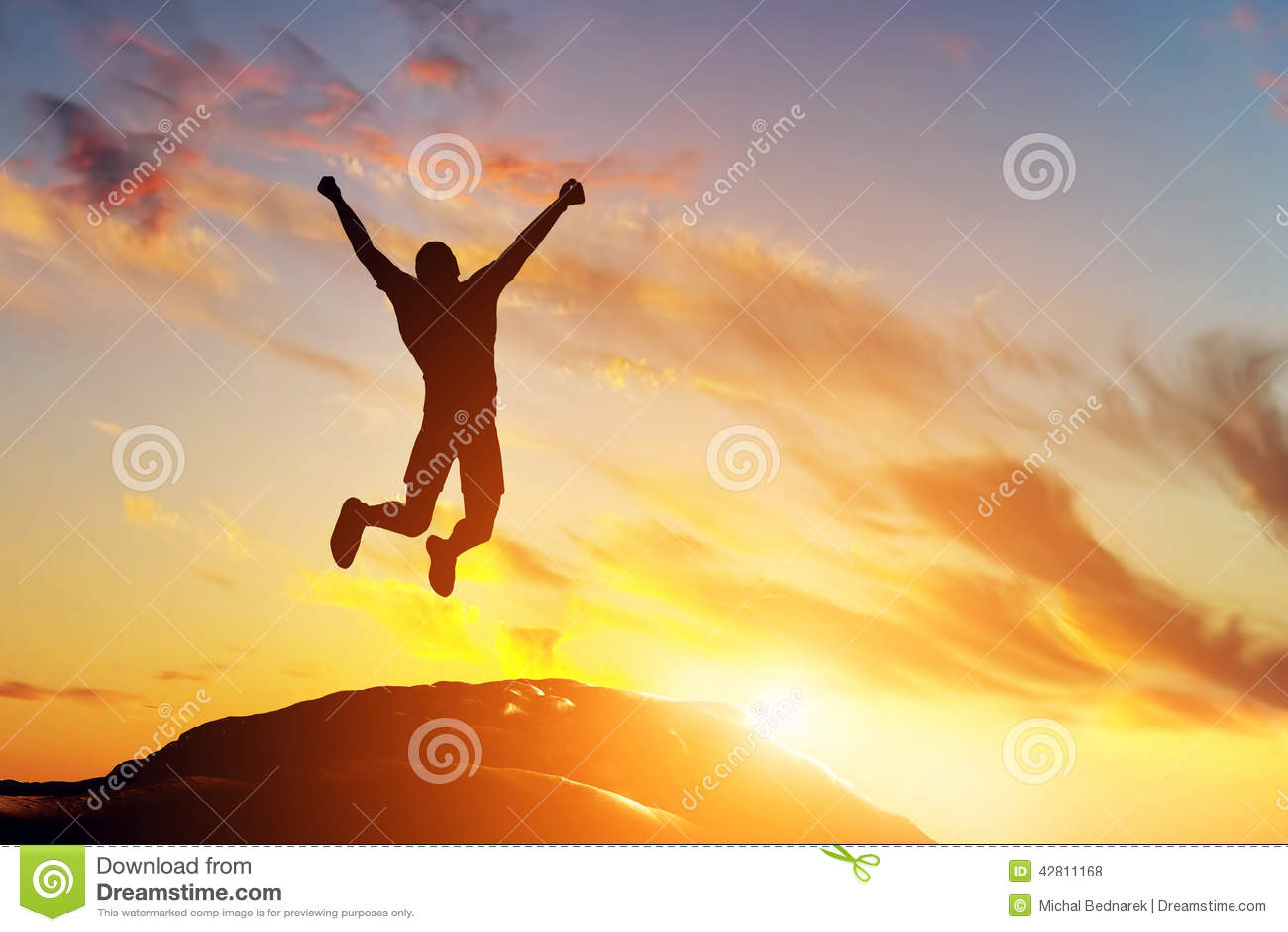 Uomo felice che salta per la gioia sul picco della montagna al tramonto Successo