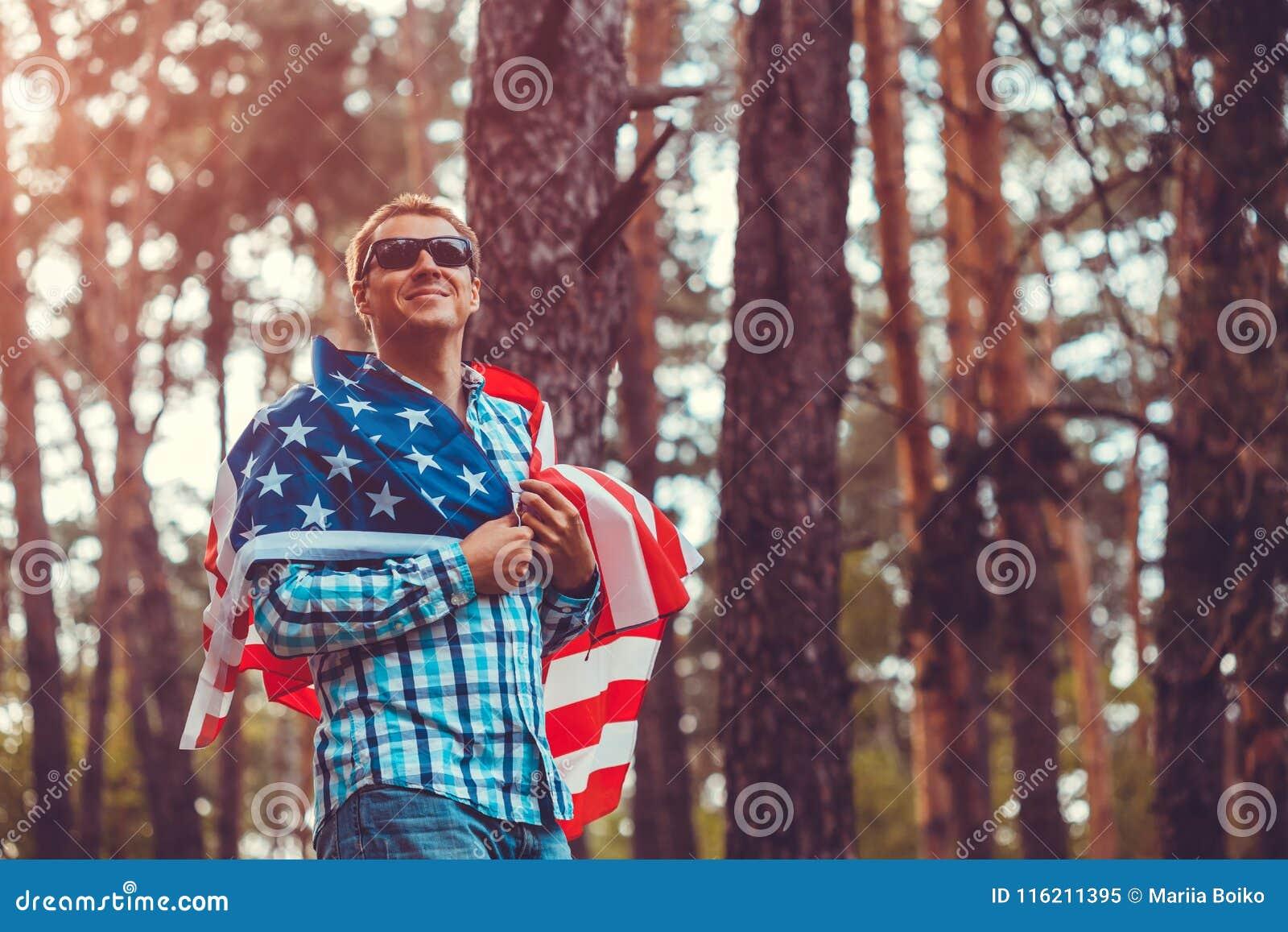 Uomo felice che tiene la bandiera di U.S.A. Celebrazione della festa dell indipendenza dell America 4 luglio Uomo che ha divertim
