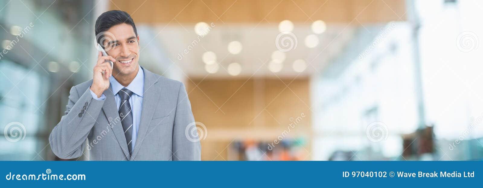 Uomo felice di affari che per mezzo di un telefono