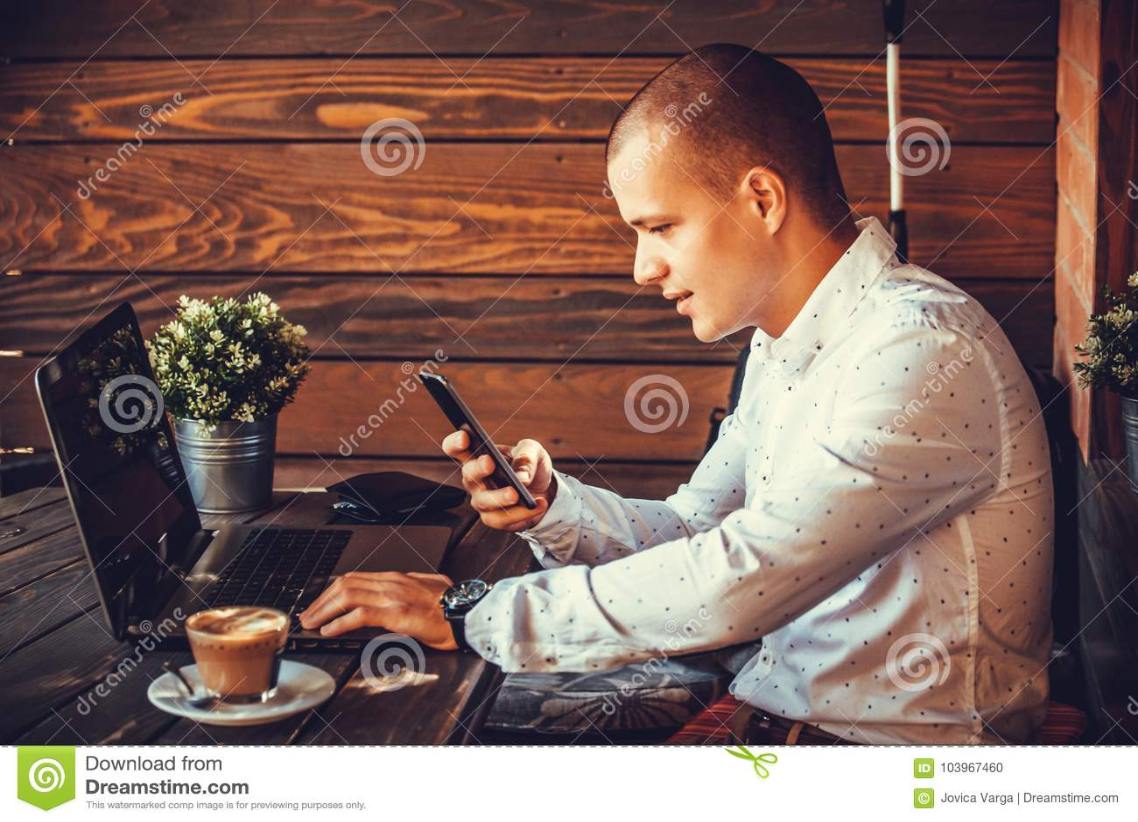 Uomo felice non retribuito che lavora con un computer portatile e uno Smart Phone