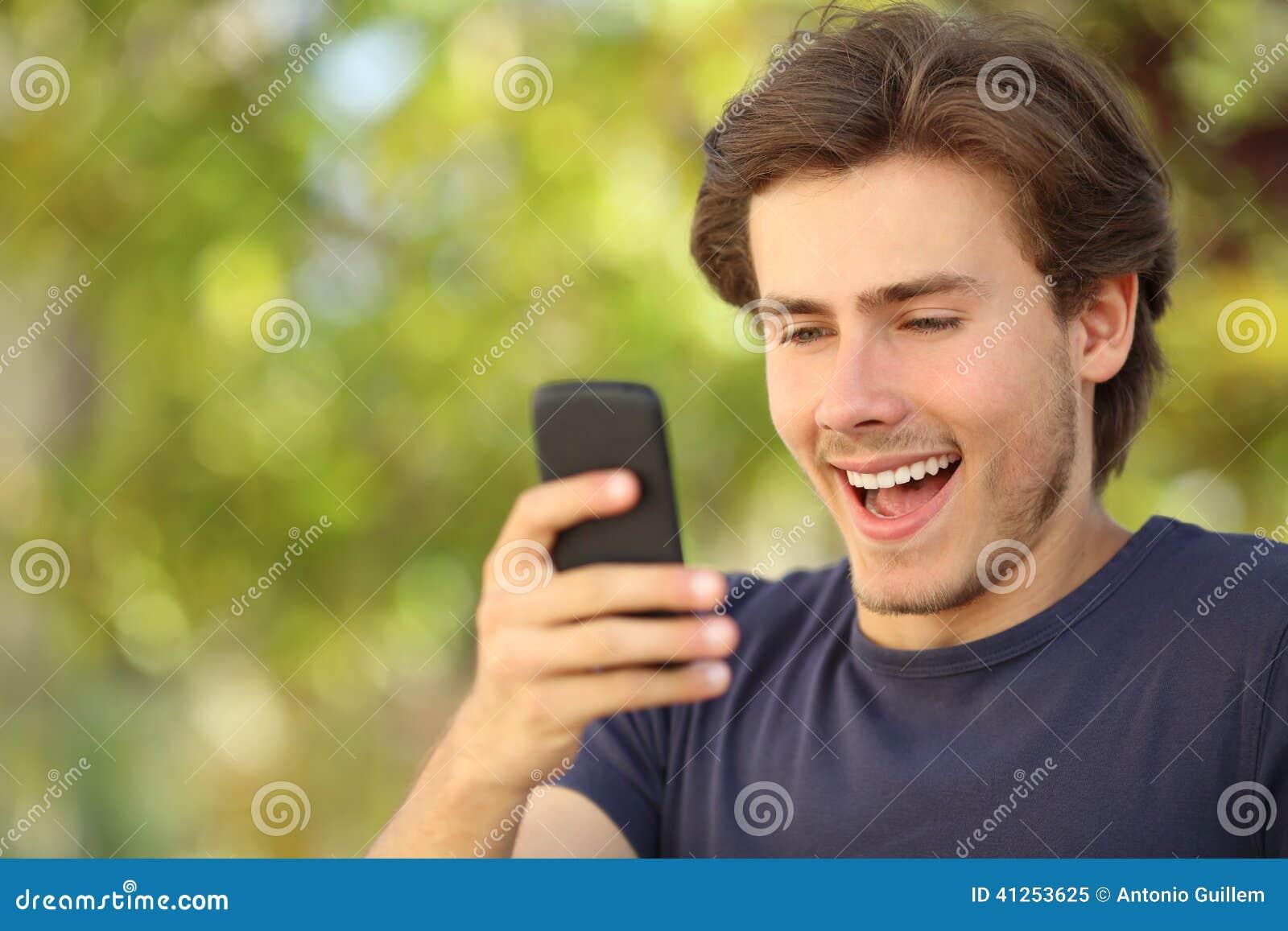 Uomo felice sorpreso esaminando lo Smart Phone
