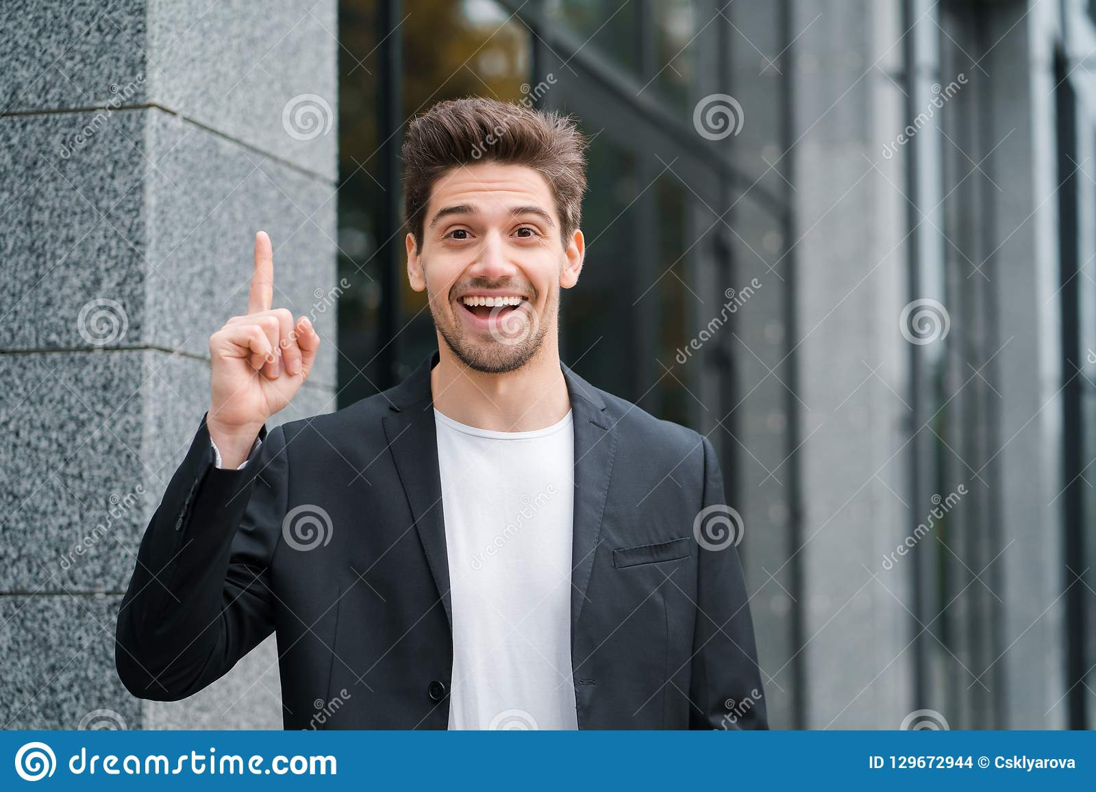 Uomo felice sorridente dello studente che mostra gesto di Eureka Ritratto di giovane uomo d affari riflettente di pensiero che ha