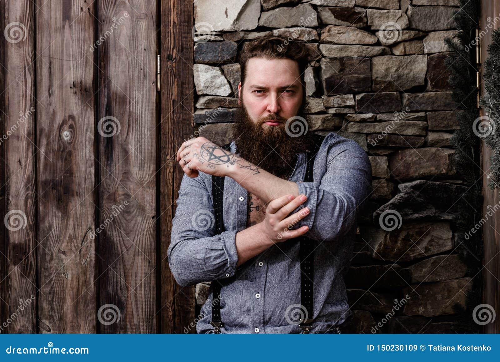 Uomo forte brutale con una barba e tatuaggi sulle sue mani vestite nei supporti alla moda dell abbigliamento casual sui precedent