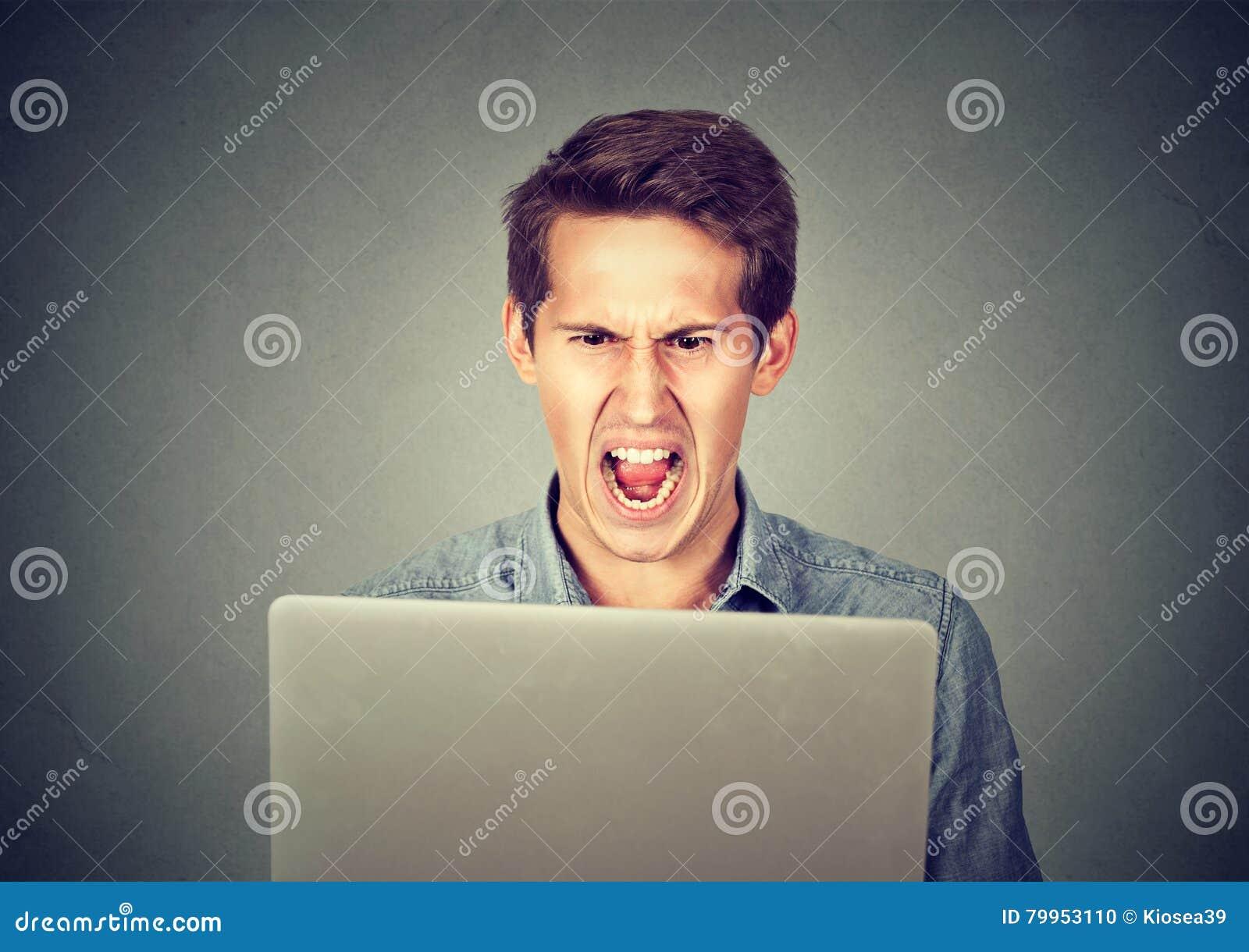 Uomo furioso arrabbiato di affari che grida al computer