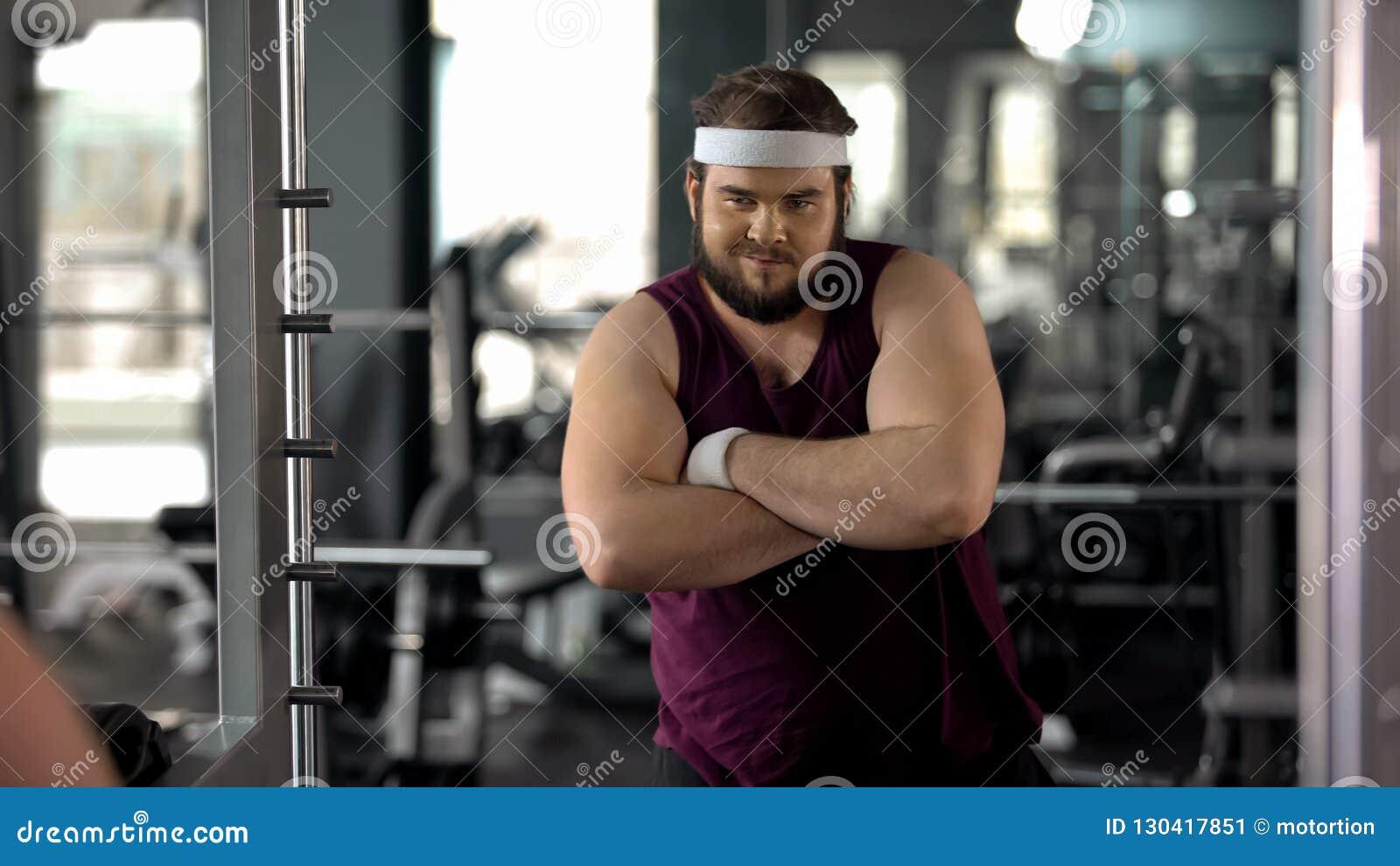 Uomo grasso con le mani piegate che esaminano specchio, soddisfatto con i risultati di perdita di peso