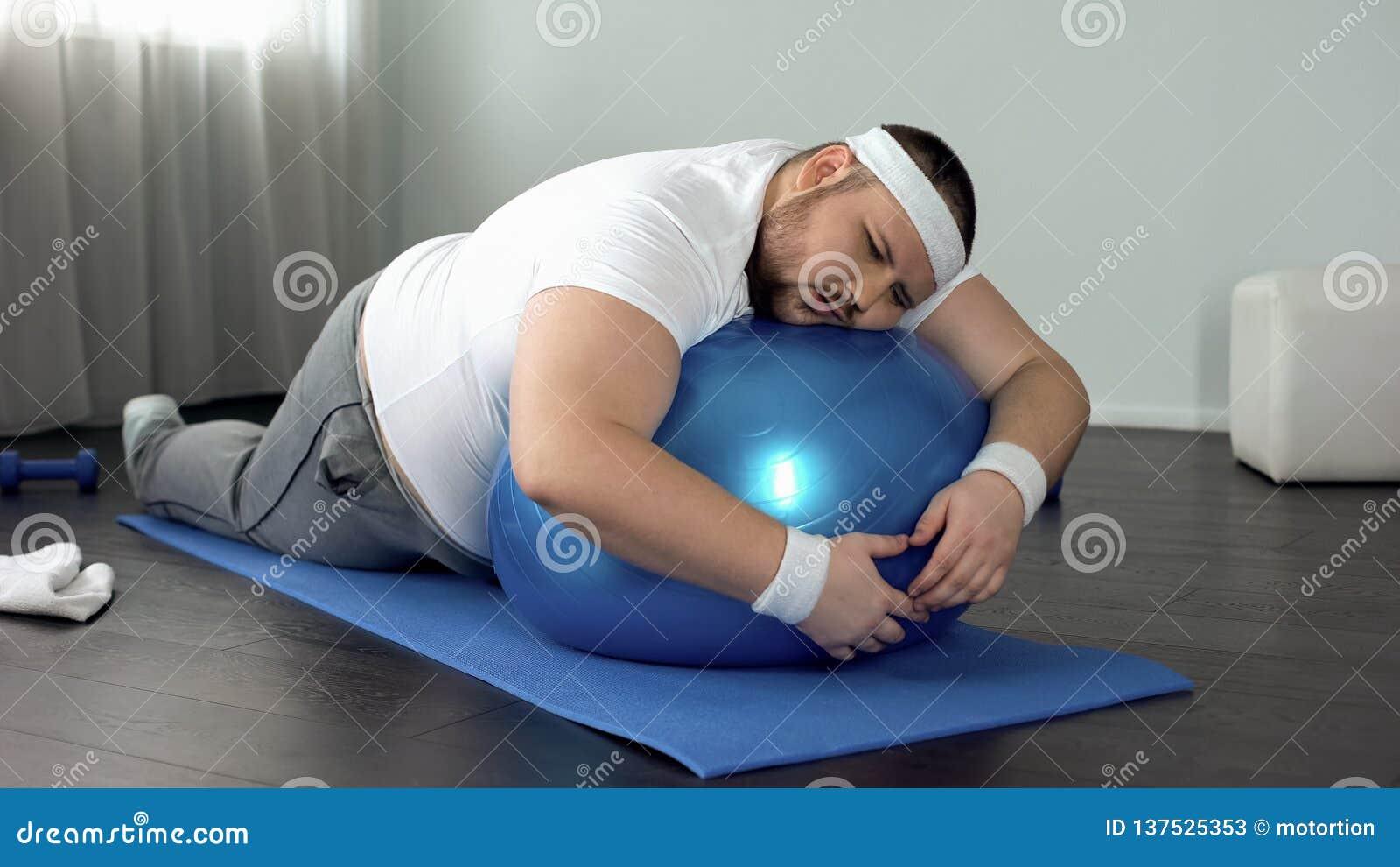 Uomo grasso Debole-voluto che si rilassa sulla palla di forma fisica, rottura domestica di allenamento, pigrizia