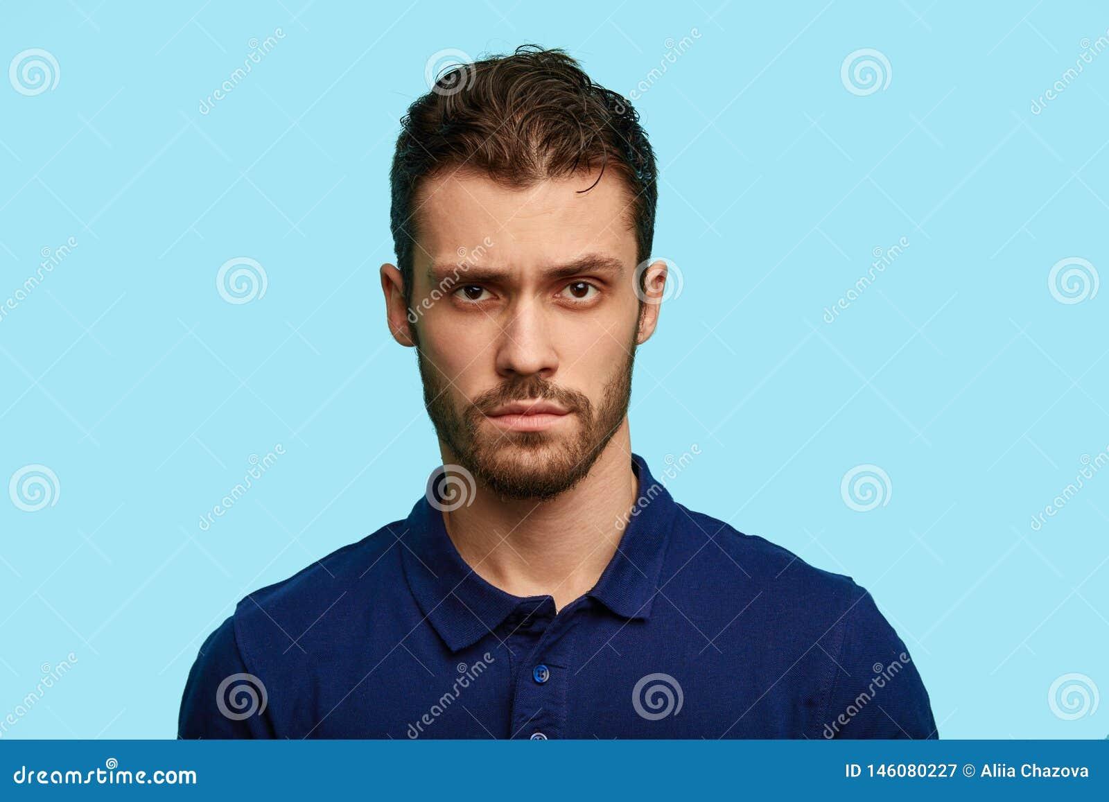 Uomo incerto non rasato scettico bello che indossa maglietta blu che posano nello studio, il suo fronte in pieno di dubbio e diff