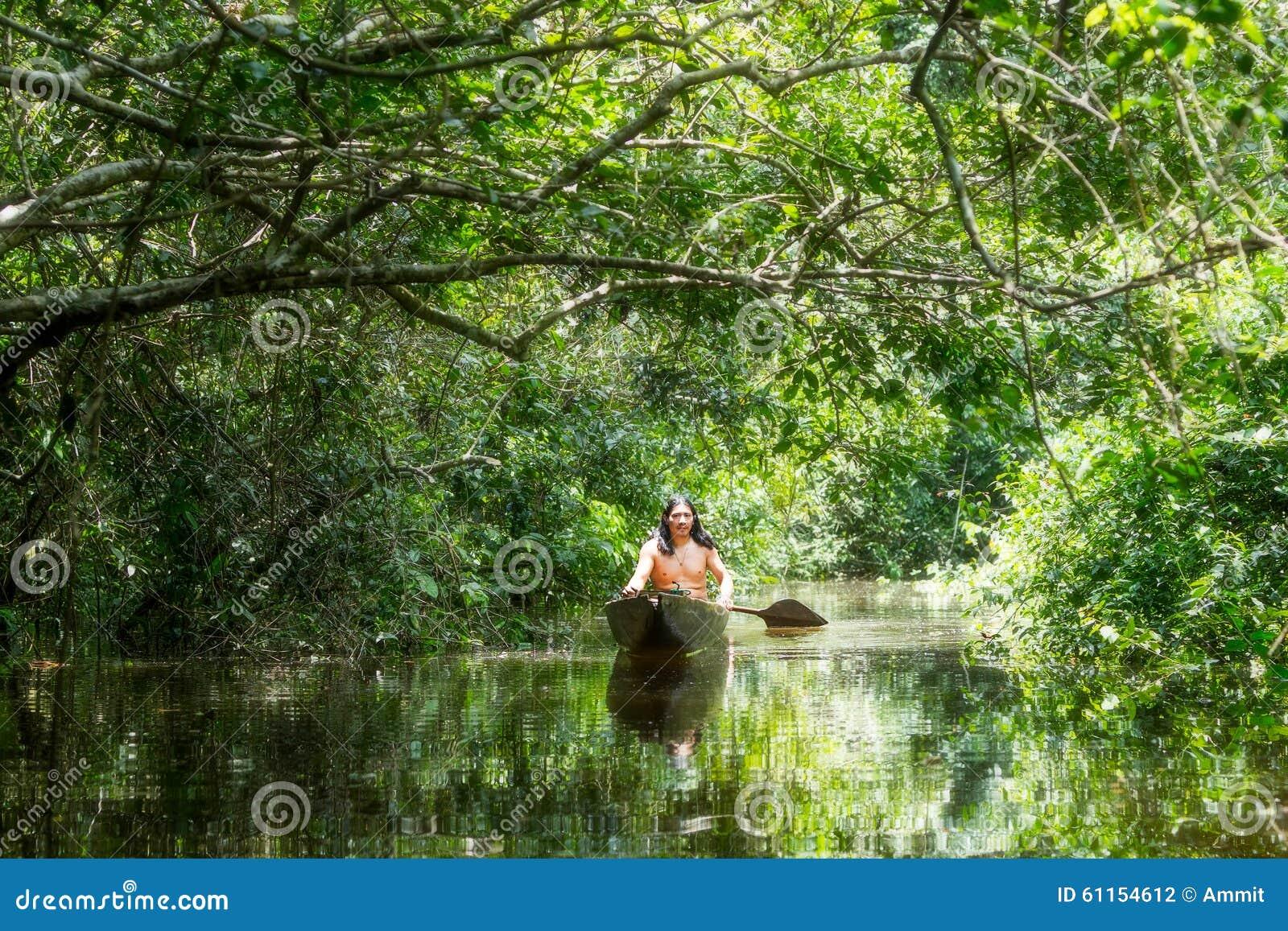 Uomo indigeno con la canoa in bacino di Amazon