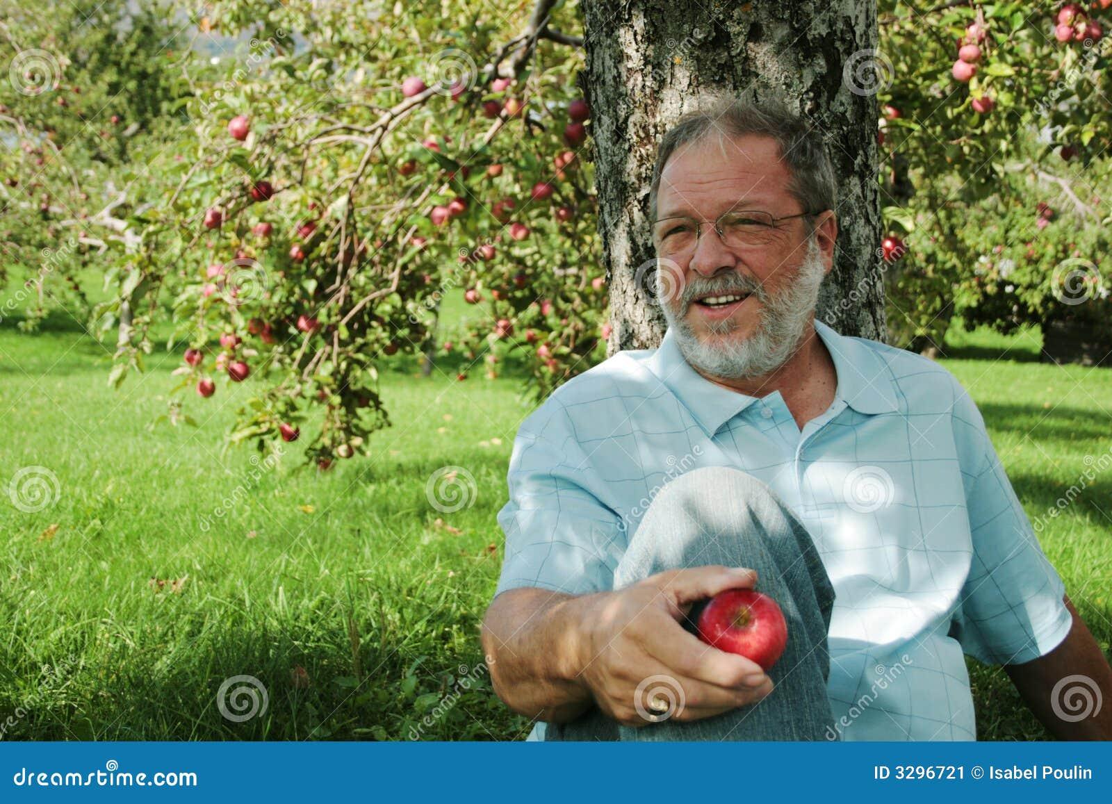 Uomo invecchiato centrale in frutteto