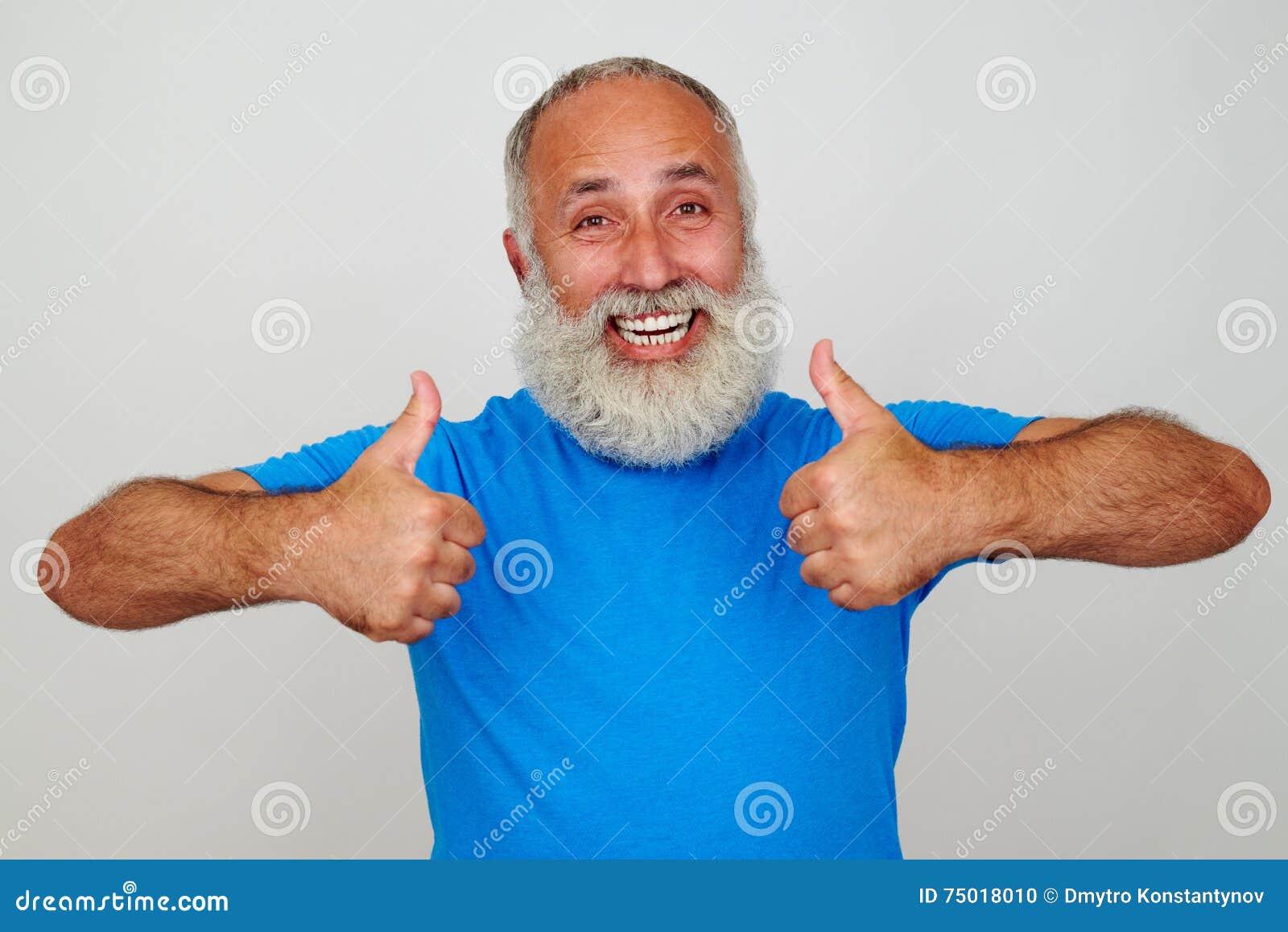 Uomo invecchiato sorridente che dà due pollici su contro il fondo bianco